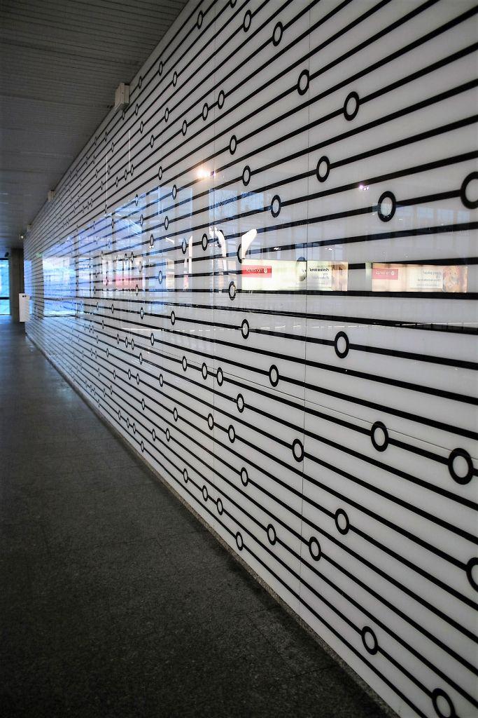 Szklany panel na ścianie starej antresoli. Identyczne panele zastosowane zostały w zmodernizowanym w 2015 r. korytarzu  zachodnim pod Al. Jana Pawła II. Fot. Jerzy S. Majewski