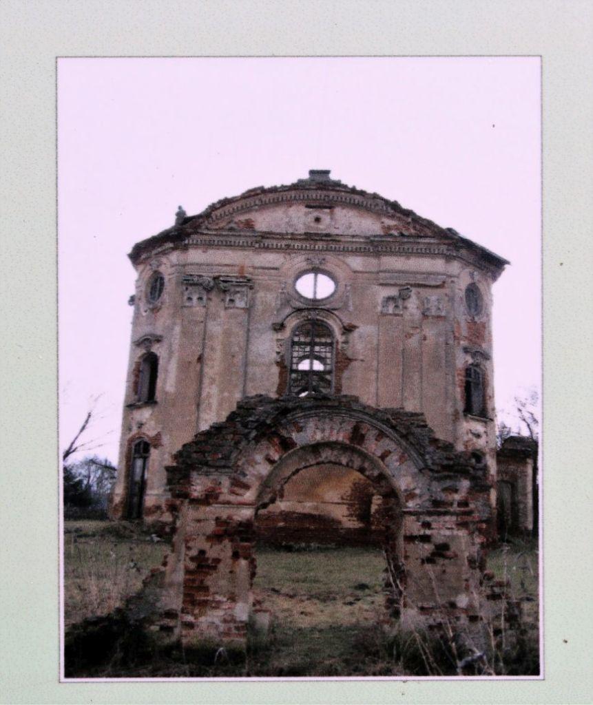 Fragment tablicy informacyjnej ze zdjęciem kościoła przed rozpoczęciem odbudowy w 2007 r.