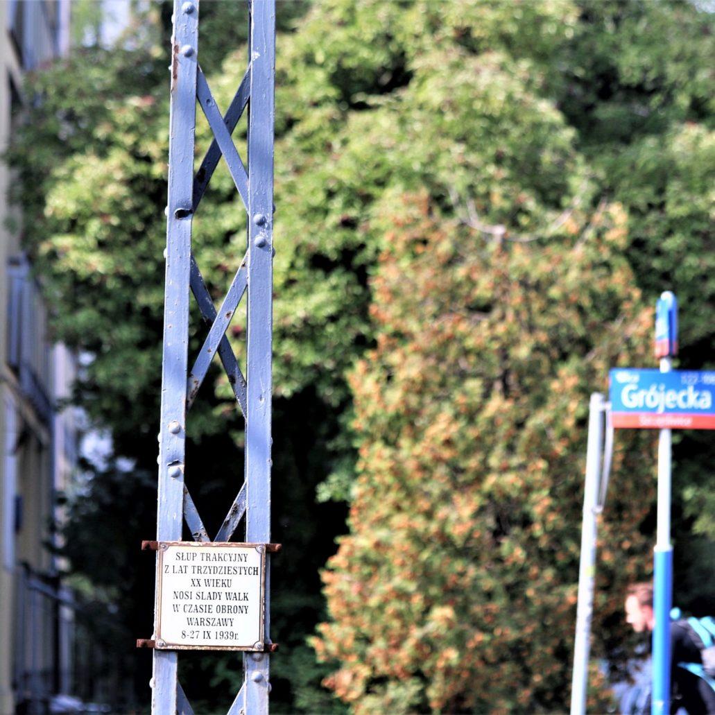 Warszawa. Słup trakcji tramwajowej na Grójeckiej ze śladami po pociskach z 1939 r. Słupy tramwajowe widnieją na dziesiątkach fotografii niemieckich, ukazujących natarcie na Ochotę. Ocalał jeden. Przetrwał do naszych czasów dzięki obrońcy zabytków Januszowi Sujeckiemu, który w 2001 r. wraz z miastem i Tramwajami Warszawskimi doprowadził do jego konserwacji. Widnieje na nim tabliczka informacyjna. Fot. Jerzy S. Majewski