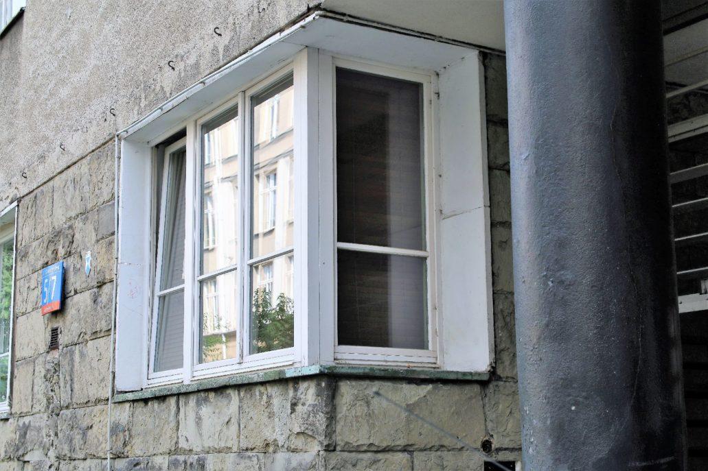 Narożne okno do kamienicy przy wejściu do bramy. Architekt w partii przyziemia zastosował chętnie stosowane w końcu lat 30 płyty z nieobrobionego kamienia. W fasadzie kontrastują one ścianą wyższych kondygnacji, które pierwotnie miały gładką wyprawę z tynku imitująca podziały płytowe. Dziś pokrywa je prymitywny tynk z czasów PRL-u