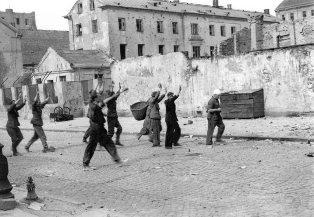"""Niemieccy jeńcy z załogi PAST-y prowadzeniu Zielną po zdobyciu budynku 20 sierpnia 1944 r. Wśród jeńców było nieco niemieckich pocztowców, ale byli też esesmani. Jeńców wraz z uwolnionymi z gmachu polskimi pracownikami centrali telefonicznej odprowadzano na punkt zborny do gmachu PKO przy Świętokrzyskiej oraz na Marszałkowską 125 do dowódcy IV Rejonu majora """"Zagończyka"""". Tam prokuratorzy i sędziowie sprawdzali każdego zatrzymanego, decydując o jego losie. Po wylegitymowaniu zwolniono polskich pracowników PAST-y. Jeden z nich, Stanisław Chmiel, zatrudniony przez Niemców w kuchni, zwrócił uwagę, że w stosunku do liczby porcji, które wydawał liczba jeńców jest zbyt mała. Tak odleziono ukrywającą się w piwnicach grupę żołnierzy Wehrmachtu i SS. SS-manów po przesłuchaniu rozstrzeliwano. Fot. Eugeniusz Lokajski """"Brok"""". Fotografia ze zbiorów Muzeum Powstania Warszawskiego. MPW-IN/661"""