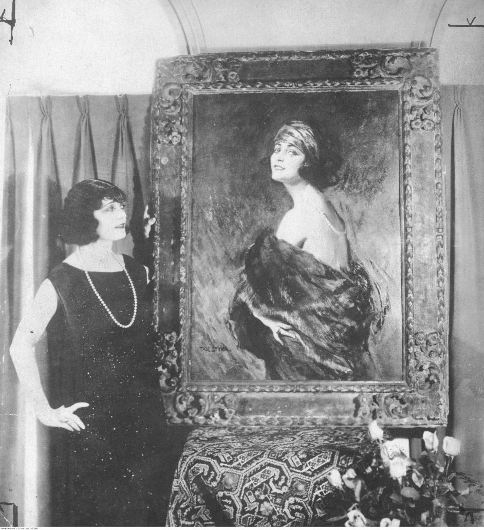 """Do kina specjalnie przychodzono dla Poli Negri. Najpierw gwiazdy warszawskiej wytwórni """"Sfinks"""", później wytwórni berlińskich wreszcie Hollywoodu. Na zdjęciu Pola Negri obok swego portretu namalowanego przez Tadeusza Stykę. Zdjęcie z 1924 r. kiedy to aktorka cieszyła się światową sławą. Fot. Narodowe Archiwum Cyfrowe."""