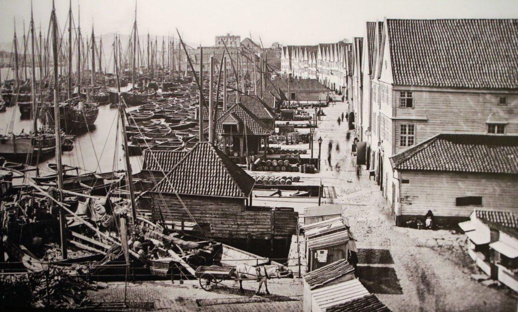 Bergen. Tak hanzeatycka zabudowa Bryggen wyglądała w 1890 r. Wzdłuż nabrzeża ciągnął się drewniany pomost przy którym cumowały statki. Przed każdym domem stała wiata magazynowa z drewnianym żurawiem za pomocą którego przeładowywano ładunki statków. Zdjęcie archiwalne stanowi fragment ekspozycji Muzeum Hanzeatyckiego w Bergen.