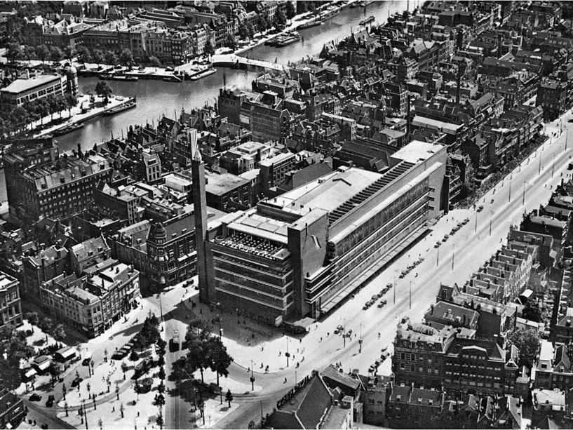 """Rotterdam. Tak w początku lat 30. XX w. wyglądał supernowoczesny dom towarowy """"De Bijenkorf"""" ukończony w 1930 r. wg projektu Willema M. Dudoka. Wznosił się przy placu w sąsiedztwie starej zabudowy. Z lewej mu dołu widać górująca nad nim wieże. Miał przeszklone, świecące nocą elewacje, schody ruchome we wnętrzach i widoczną na zdjęciu kawiarnię na płaskim dachu. Fotografia z Wikipedii."""