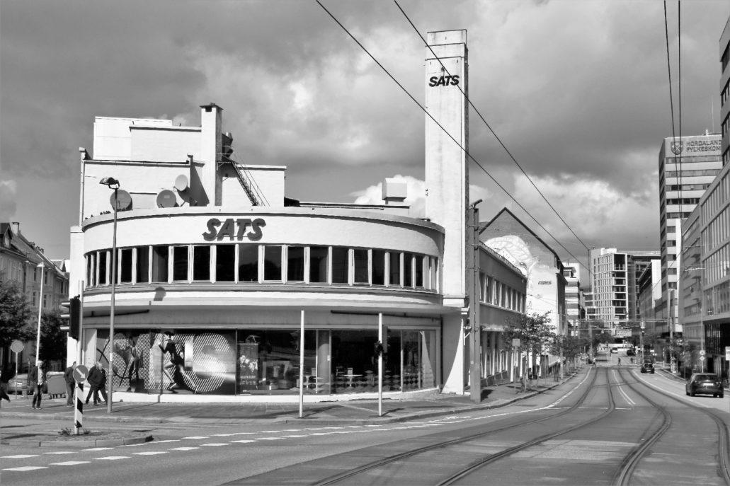 """Bergen Lars Hillesgate. Pełen ekspresji budynek handlowy z 1938 r. mieszczący dziś siłownię SATS. Podobnie jak w domu towarowym """"Sundt"""" funkcję znaku pełni wysmukła wieża-iglica. Za budynkiem, któremu grozi nadbudowa znajduje się nieczynna już stacja benzynowa z 1928 r. Fot. Jerzy S. Majewski"""