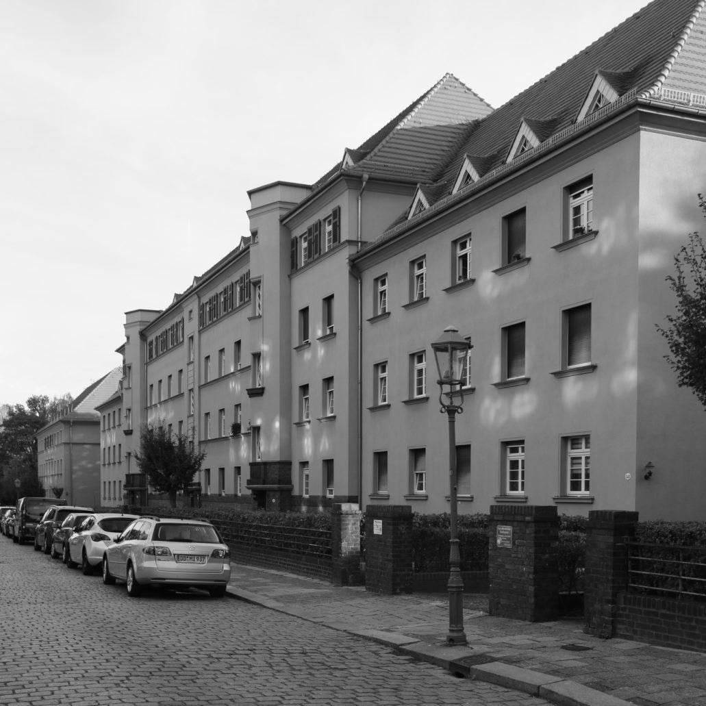 """Drezno. Wohnhof Eisenbahnergenossenschaft. Środkowy, wydłużony blok od strony Malterstr. Kompozycja budynku i pierzei złożonej z trzech bloków jest symetryczna. Dominantę stanowi wyższa i zryzalitowana część środkowego bloku. Ożywiają ją po bokach dwie """"pryzmatyczne"""" wieże klatek schodowych. W oknach widoczne zielone żaluzje. Fot. Jerzy S. Majewski"""