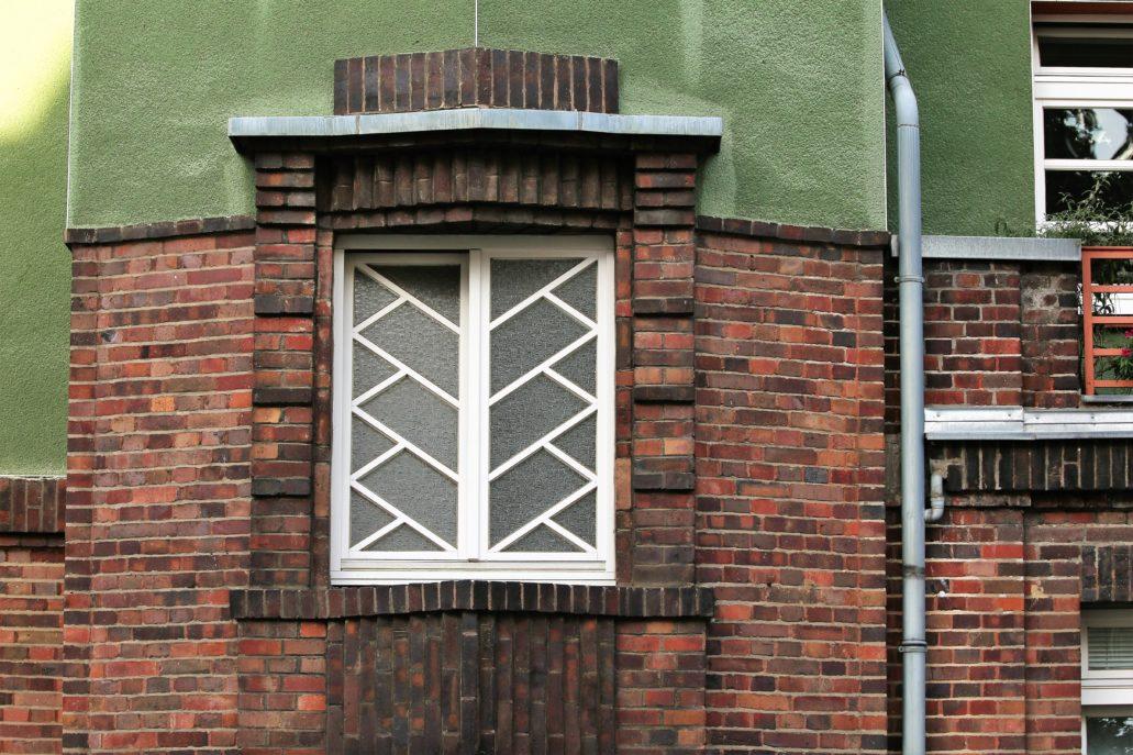 Drezno. Wohnhof Eisenbahnergenossenschaft. Okno klatki schodowej w bloku ze sklepami od strony Deubnerstr. Układ szprosów powtarza się w innych klatkach o pryzmatycznych podstawach. Fot. Jerzy S. Majewski