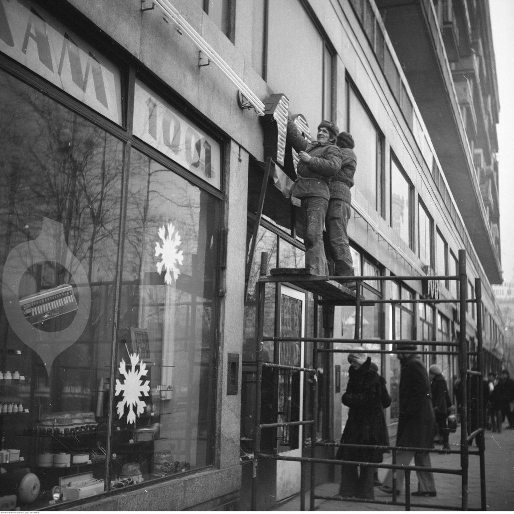 """Warszawa. Montaż neonu sklepu """"1001 drobiazgów"""" przy ul. Świętokrzyskiej. Zdjęcie z lat 60. XX w. Fot. Narodowe Archiwum Cyfrowe"""