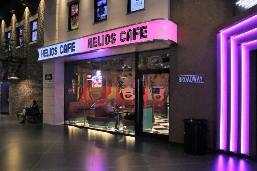 Warszawa. Wnętrze nowego kina Helios w CH Blue City jest wykreowaną scenografią, łączącą klimat dawnych warszawskich kin z wielkomiejskością Nowego Jorku. Stremline'owy fryz z napisem Helios Cafe. Pod nim dwa ażurowe neony. Fot. Jerzy S. Majewski.