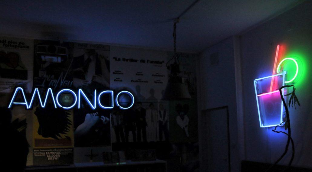Neonowy napis AMONDO wisi na ścianie we wnętrzu kina. Po prawej stronie drink – jeden z nielicznych, do dziś zachowanych neonów pastelowych, których nie produkuje się już od ponad dwudziestu lat. Fot. Jerzy S. Majewski.