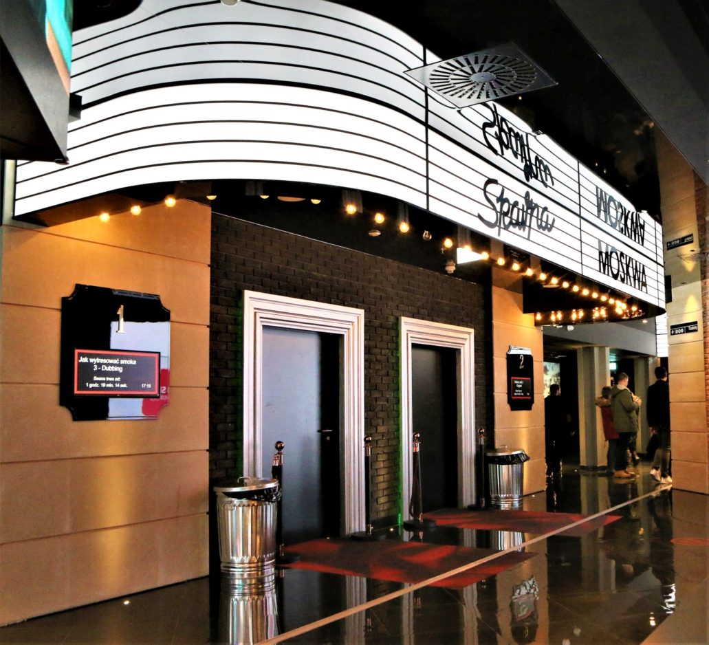"""Wnętrze kina Helios. Napisy nad stylizowanymi portalami do sal nawiązują do neonów dawnych warszawskich kin. Tutaj legendarne """"Skarpa"""" i """"Moskwa"""". Elementem nawiązującym do broadwayowskiego charakteru są duże żarówki rzucające klimatyczne, złote światło. Fot. Jerzy S. Majewski."""