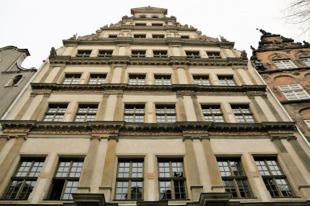 Gdańsk, Chlebnicka 16. Fragment fasady Domu Anielskiego. W trakcie przeprowadzonej niedawno renowacji elewacji odtworzono złocenia fryzów oraz innych dekoracji architektonicznych. Pomiędzy oknami widać pary pilastrów dźwigających belkowanie. Budynek wzniesiono w XVI w. na podwójnej działce i jest dla tego jest on dwukrotnie szerszy od większości innych kamienic mieszczańskich miasta. Był też największą kamienicą mieszkalną Gdańska sprzed epoki rozbiorów. Fot. Jerzy S. Majewski