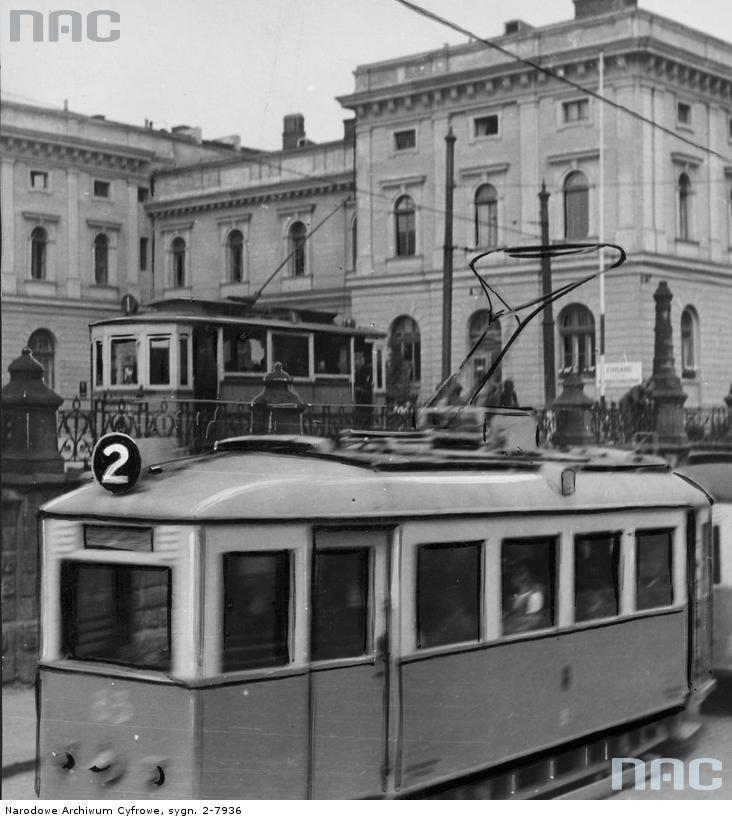 Kraków. (Sieć tramwaju elektrycznego uruchomiona w 1900 r.) Mało kto dziś wie, że w dobie monarchii Austriackiej w Krakowie, obowiązywał ruch lewostronny. W niepodległej Polsce wprowadzono w mieście ruch prawostronny, ale tramwaje jeździły lewostronnie jeszcze do 1925 r. Moim ulubionym miejscem dla obserwowania krakowskich tramwajów jest wiadukt przy ul. Lubicz, wzniesiony w czasach monarchii i przyozdobiony inicjałami cesarza Franciszka Józefa. Na zdjęciu tramwaj wyjeżdżający spod wiaduktu przy ul. Lubicz. Fot. NAC.