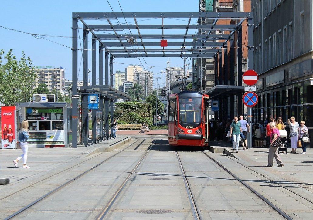 Śląsk. Ilekroć myślę o tramwajach w miastach Zagłębi i Górnego Śląska przypomina mi się wyprawa sprzed lat gdy wsiadłem do tramwaju w Sosnowcu i z przesiadkami dotarłem ostatecznie do Gliwic. Trwało to wieki ale wysiadając obejrzałem centra kilku miast. Wydaje mi się, że w każdym mieście musiałem wówczas kupować inny bilet. Dziś obowiązuje wspólny bilet, gdyż wszystkie linie konurbacji górnośląskiej obsługują malowane na czerwono Tramwaje Śląskie. Na zdjęciu jeden z przystanków na Rynku w Katowicach . Nad nich charakterystyczny ażurowy fantom budynku, wyznaczający linię zabudowy danej pierzei Rynku. Fot. Jerzy S. Majewski