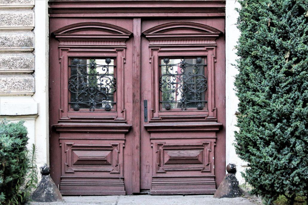 """Bardzo popularne w Łodzi odboje w kształcie odwróconych lejków, bądź czapeczek z pomponikami, chroniące narożniki przejazdu bramnego pałacowej budowli przy Pomorskiej 16a. Warto zwrócić uwagę na piękne, drewniane wierzeje bramy. W czasach PRL-u w Łodzi dokonano masowego """"bramobójstwa"""" usuwając większość zabytkowych wierzei. Dziś w przytłaczającej większości kamienic są one zastąpione prymitywnymi kratami. Fot. Jerzy S. Majewski"""