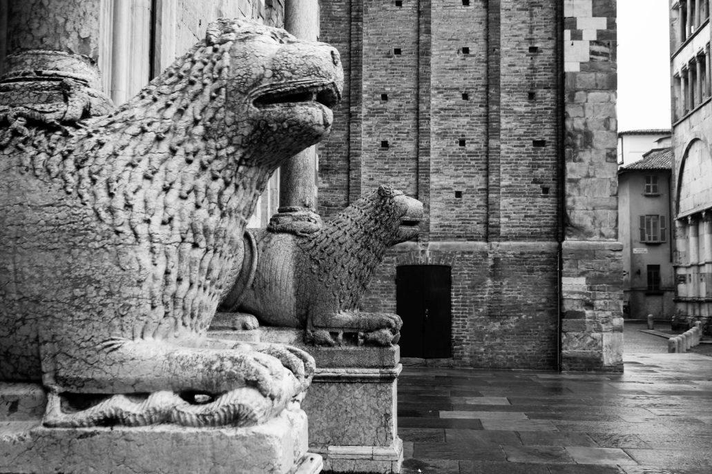 Parma. Piazza Duomo. Romańskie lwy dźwigające kolumny w portalu katedry. W głębi przyziemie gotyckiej kampanili budowanej przez dziesięć lat od roku 1284. Fot. Jerzy S. Majewski
