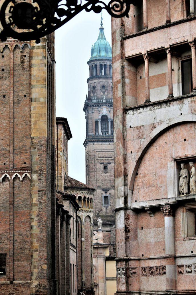 Parma. Widok z Piazza Duomo na wieżę kościoła San Giovanni Evangelista Benedyktynów. Z lewej fragment wieży katedry, z prawej romańskiego baptysterium. Fot. Jerzy S. Majewski