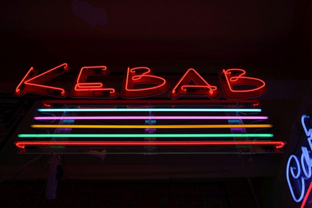 """Neon """"Kebab"""" – czerwone, stylizowane litery na podkładzie; pod nim proste, ażurowe kolorowe rurki neonowe. Fot. Jerzy S. Majewski"""