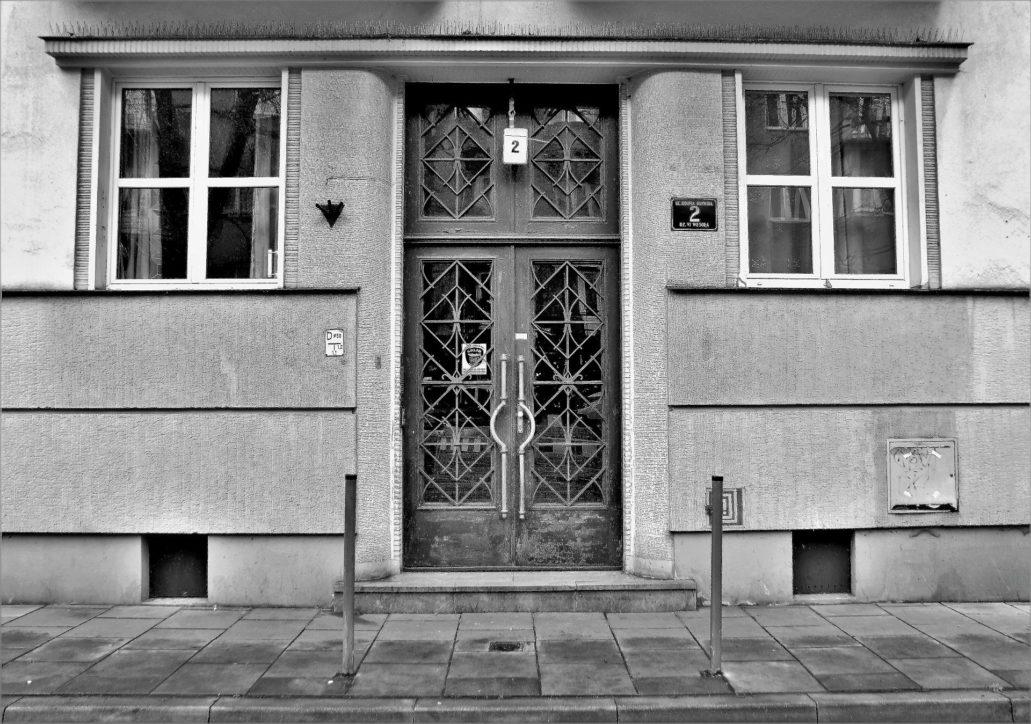 Kraków. Bujwida 2. Strefa wejścia z portalem. Zwracają uwagę częste w architekturze lat 30. zaokrąglone ościeża. Podobnie jak w sąsiedniej kamienicy pod nr 1, i tutaj zarówno portal, jak i obramienia okien ujęte są w rowkowane obramienia. Również wyodrębniona partia cokołowa jest boniowana, co sprawia wrażenie solidnego osadzenia domu. I ten budynek wykończył po wojnie architekt Stanisław Zydroń. Fot. Jerzy S. Majewski
