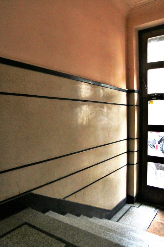Kraków. Bujwida 10. Kamienica powstała w 1936 r. według projektu Henryka Rittermana. Westybul ma efektownie zaprojektowane i starannie wykonane ściany z lastryko. Niestety dziś jest to najbardziej zaniedbane przy ulicy wnętrze klatki schodowej. Fot. Jerzy S. Majewski
