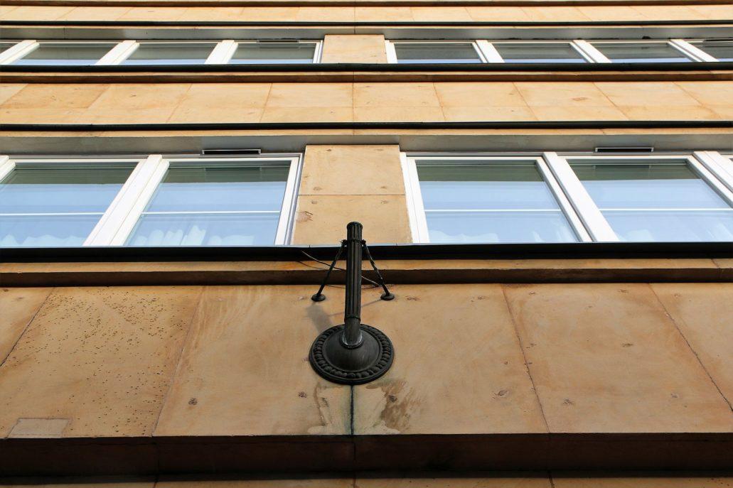 Warszawa. Koszykowa 10. Pamiątką po ambasadzie węgierskiej jest uchwyt na flagę, umieszczony ponad wejściem do budynku pomiędzy oknami pierwszego piętra.