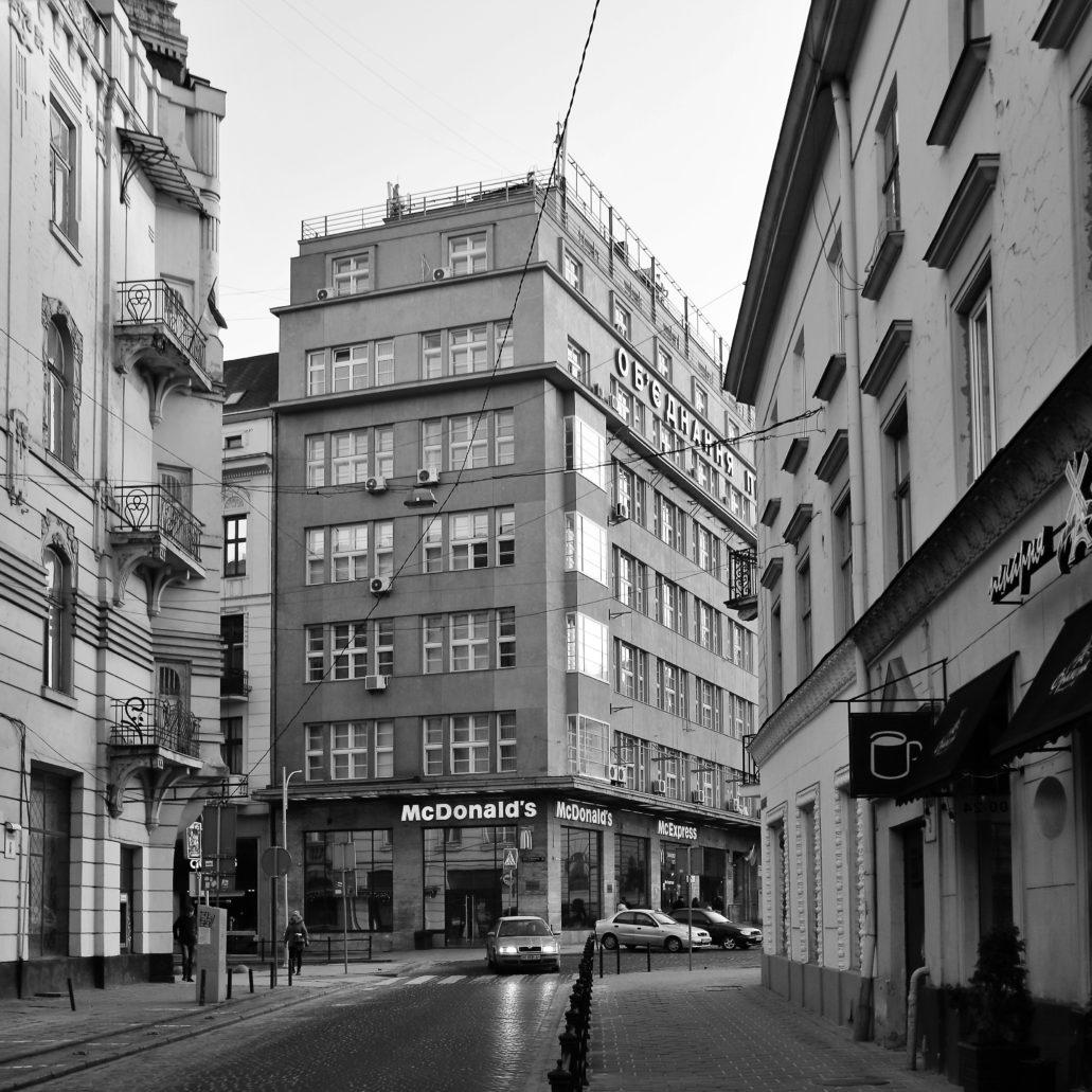 """Lwów. Kamienica Sprechera w perspektywie dawnej ulicy Chorążczyzny (dziś Czajowskiego). Boczna elewacja biurowca jest wąska i wysmukła. Widać stąd też uskokowe cofanie się górnych kondygnacji mieszczących pierwotnie mieszkania i wzbogaconych o tarasy. Także w budowanym od 1929 r. warszawskim drapaczu chmur """"Prudential"""" ostatnie kondygnacje są nieco cofnięte w stosunku do elewacji niższych partii wieży i przeznaczone zostały na apartamenty do wynajęcia. Fot. Jerzy S. Majewski"""