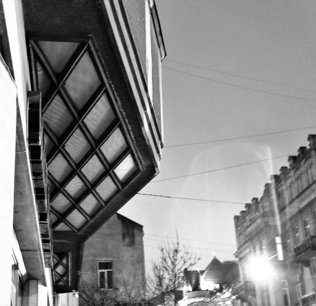Lwowscy architekci w latach 30. bawili się światłem. Powtarzali efekt oświetlenia ściany parteru szklanymi plafonami umieszczonymi pod daszkiem obiegającym przyziemie. Rozwiązanie nadawało ulicy wrażenie wielkomiejskości. Resztki takich plafonów wciąż można zobaczyć w kamienicy bankiera Ozjasza Grüssa przy dawnej ulicy Sykstuskiej 30 (dziś Doroszenki). Z kolei w widocznym na zdjęciu Domu Notariuszy przy Romanowicza 8 (dziś bulwar kniazia Romana), zaprojektowanym przez Zbigniewa Wardzałę, kryształkowe plafony umieszczono nie pod daszkiem, lecz trójkątnymi wykuszami. Jeszcze bardziej pomysłowe rozwiązanie zastosowano w sąsiednim domu dr. Zbigniewa Rychłowskiego pod nr 6, gdzie światło przenikało przez dwa rzędy luksferów. Tworzyły linię światła stanowiącą rodzaj świetlnego fryzu ponad lekko podciętym parterem. Elegancka ulica Romanowicza stanowiła przedłużenie Akademickiej z rozjarzonym światłem domem Sprechera. Niestety w żadnym z trzech ze wspomnianych budynków elementy oświetlenia od dawna nie działają. Fot. Jerzy S. Majewski