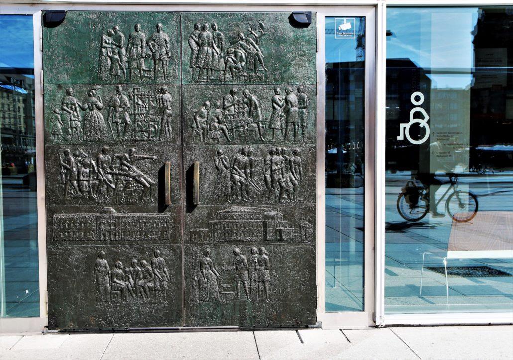 Drezno. Kulturplast. Do reprezentacyjnego holu wejściowego na parterze prowadzi pięć par drzwi odlanych w brązie przez drezdeńską odlewnię Primer&Franz. Masywne, kontrastują z eteryczną ścianą ze szkła, w której są osadzone. Zaprojektował je zmarły w ubiegłym roku rzeźbiarz Gerd Jaeger. Są ideowo mniej ideologiczne od dekoracji malarskich. Wyobrażają scenki stanowiące opowieść o dziejach Drezna od czasów niewielkiej wioski rybackiej, po wielkie miasto. Fot. Jerzy S. Majewski
