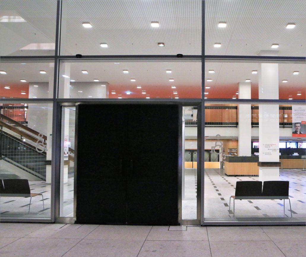 Drezno. Kulturpalast. Rozświetlone, widoczne od zewnątrz wnętrze hallu z ciemnym prostokątem drzwi osadzonych w szklanej ścianie. Ważnym elementem współczesnego wyglądu wnętrza jest oświetlenie. Fot. Jerzy S. Majewski