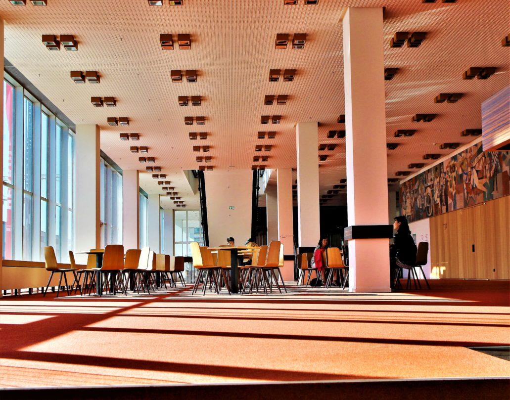 """Drezno Kulturpalast. Wnętrze hallu pierwszego piętra z widocznym po prawej stronie fryzem """"Nasze socjalistyczne życie"""". W trakcie renowacji staranie odtworzono wystrój wraz z charakterystycznym podwieszanym sufitem i zintegrowanymi z nim elementami oświetlenia. Bardzo dobrze zostały też dobrane meble, takie jak typowe dla stylistyki lat 60. lekkie krzesła. Fot. Jerzy S. Majewski"""