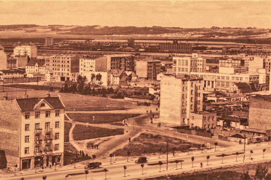 Widok Gdyni w latach 20. XX wieku. Na pierwszym planie słabo jeszcze zabudowana ulica Świętojańska. Prostopadle do niej, pośrodku, dzisiejsza ulica AK. Przy niej widoczna od tyłu, samotna kamienica przy Antoniego Abrahama 39. Na prawo od niej widać drewniane budki i po drugiej stronie ulicy parterowe zabudowania. Gdy w 1925 r. spłonęła hala targowa na obecnym Placu Kaszubskim, targowisko przeniesiono w rejon ul. Abrahama. Stąd rzędy bud. Zanim Jaszczyńscy kupili posesję u zbiegu 10 lutego i Abrahama poprzedni właściciel rozważał wzniesienie w jej miejscu hali targowej. Fotografia z ekspozycji w Muzeum Emigracji