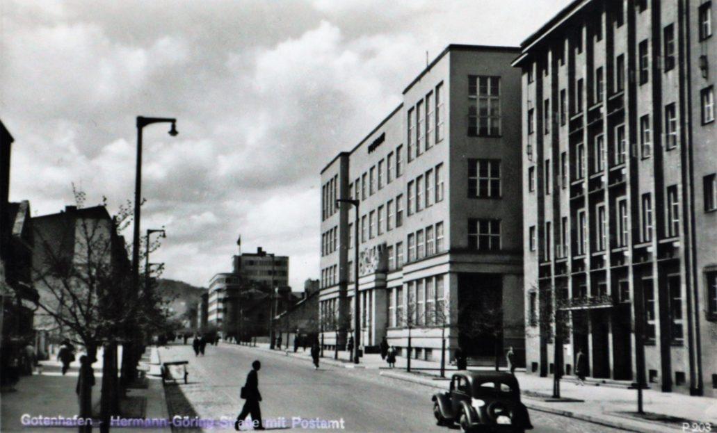 Gdynia. Ulica 10 lutego z gmachem BGK oraz Poczty po prawej stronie. Z lewej widać niewielki fragment ściany kamienicy Jaszczyńskich. Pomimo planów przebudowy pozostawała niezmieniona od 1934 r. Uwagę zwracają charakterystyczne, betonowe słupy latarni. Pocztówka wydana w czasie okupacji niemieckiej ze zbiorów autora