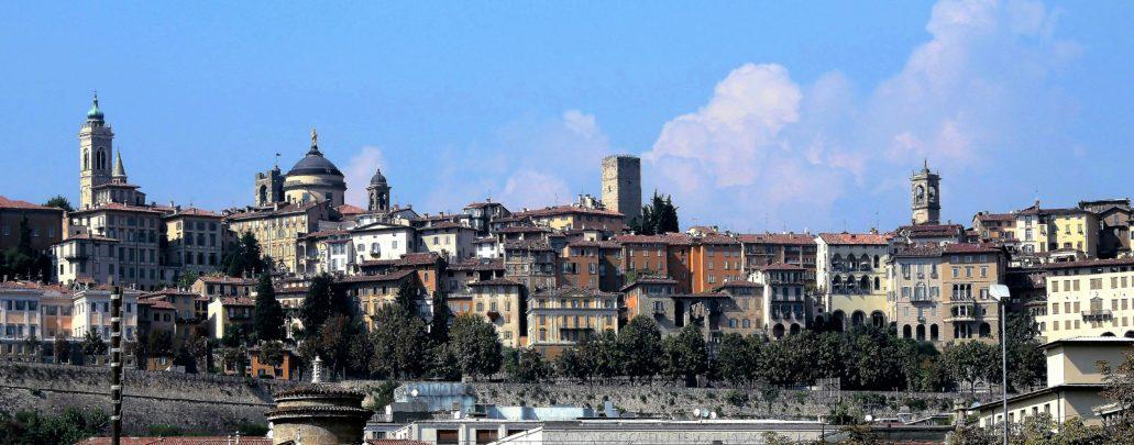 Panorama Górnego Miasta w Bergamo od strony dworca kolejowego. Od lewej wieża…. Za nią na prawo fragment Campanone, czyli wieży miejskiej przy Piazza Vecchia, obok kopuła katedry di Sant'Alessandro. Dalej, pośrodku zdjęcia XII-wieczna szlachecka wieża obronna Torre del Gobito. W średniowieczu w panoramie Wysokiego Bergamo widniało ponad trzydzieści szlacheckich wież obronnych. Z prawej jeszcze jedna, nadbudowana wieża przy Via Solata. Na pierwszym planie widać fragmenty weneckich murów obronnych. Fot. Jerzy S. Majewski