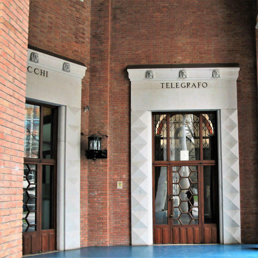 Ferrara. Palazzo delle Poste. Szerokiemu portalowi w podcieniach budynku towarzyszą mniejsze ujmujące drzwi do różnych pomieszczeń. Ich ościeża są kryształkowe. Fot. Jerzy S. Majewski
