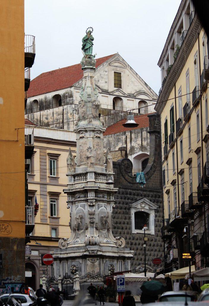 Neapol. Piazza Gesu Nuovo. Guglia dell'Immacolata. W tle masyw kościoła Jezuitów Gesu Nuovo, powstałego w latach 1584-1601. Fragmenty murów fasady pochodzą jeszcze z XV wieku, gdy wznosił tu pałac. Fot. Jerzy S. Majewski