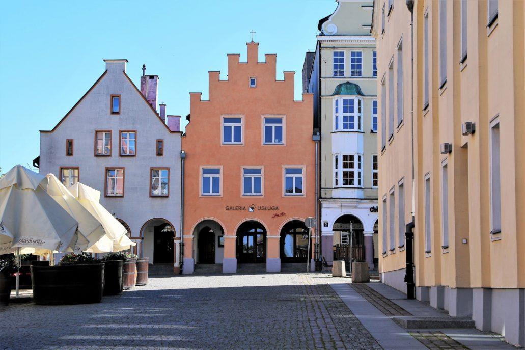 """Olsztyn. Ocalałe ze zniszczeń wojennych kamienice po północnej stronie Rynku (od lewej nr 1 oraz 2). W drugiej kamienicy od lewej przed wojną mieściła się najstarsza w mieście apteka """"Pod Orłem"""", założona w 1751 r., czyli w czasach, gdy Warmia znajdowała się jeszcze w granicach Królestwa Polskiego. W trakcie prowadzonej w latach 50. odbudowy zabudowań wokół Rynku rozważano rozebranie charakterystycznego, schodkowego szczytu ponad kamienicą i zastąpienie go bardziej """"polskim"""" szczytem barokowym. Szczęśliwie pomysłu tego nie zrealizowano. Z prawej fragment elewacji Starego Ratusza. Fot. Jerzy S. Majewski"""