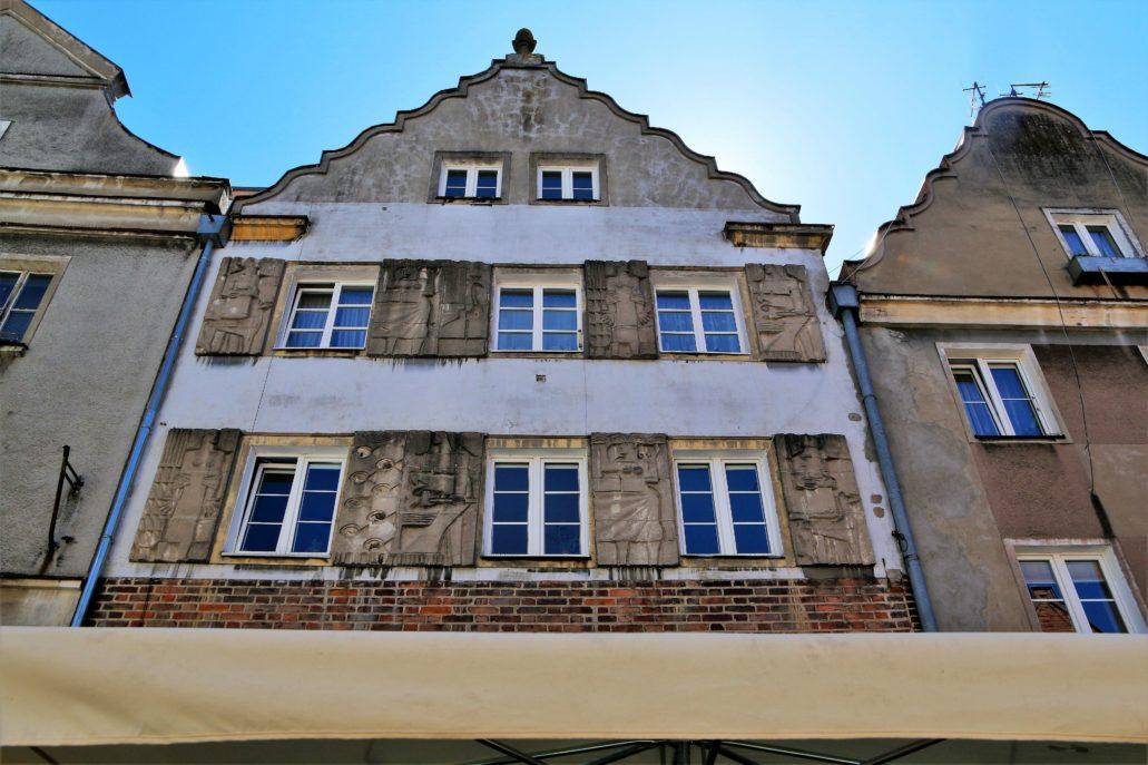 Olsztyn. Rynek Starego Miasta 11. Dom Burmistrza (Bürgermeisterhaus) uchodzi za najstarszą murowaną kamienicę Olsztyna, powstałą około 1500 r. W trakcie odbudowy został jednak dość znacznie zmieniony przez nadbudowę o piętro (podobnie jak sąsiednia kamienica). Zwieńczono go identycznym szczytem, jak przed wojną, zaś w przyziemiu odsłonięto (niewidoczne na zdjęciu) ceglane ściany podcienia o ostrych, gotyckich łukach arkad. Autorem współczesnych płaskorzeźb na fasadzie był rzeźbiarz Ryszard Wachowski, uczeń Xawerego Dunikowskiego. Fot. Jerzy S. Majewski