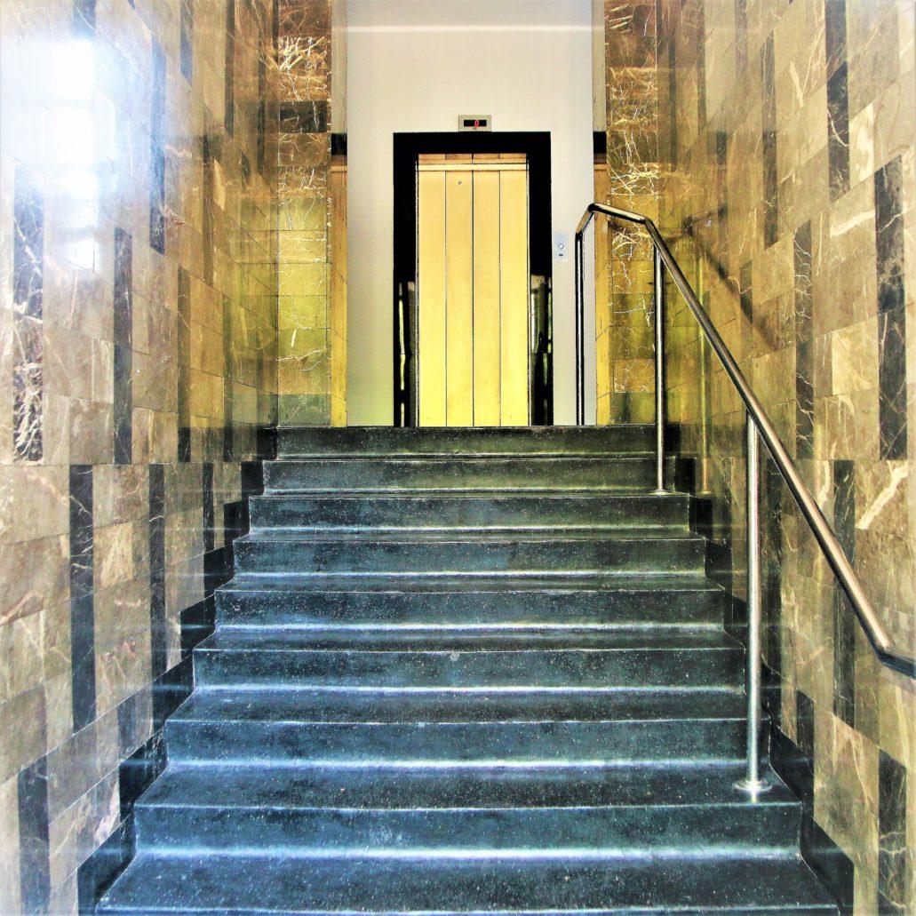 """Warszawa. Al. Niepodległości 156. Westybul ze schodami. Jego ściany obłożone zostały kawowym marmurem. Podobnie jak w części sąsiednich kamienic. Winda jest współczesna. Oryginalna z 1938 r., dostarczona była przez firmę """"Stigler"""". Schody wiodą na wysoki parter. W tylnym trakcie od podwórka na wysokim parterze znalazło się mieszkanie dwupokojowe oraz mieszkanie dla dozorcy kamienicy. Fot. Jerzy S. Majewski"""