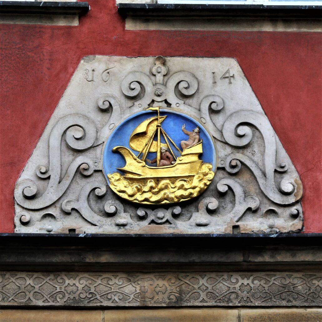 """Świdnica. Rynek 26. Dom """"Pod złotym okrętem"""". Wyzłocone godło kamienicy z datą 1614. Okręt, czy może raczej statek dobrze symbolizuje kupieckie ambicje świdnickich mieszczan. Z drugiej strony, jak pisze Sobiesław Nowotny w książce o kamienicach wokół świdnickiego rynku, był on aluzją do nazwiska właściciela kamienicy, aptekarza Jakoba Schiffa. Schiff to po niemiecku okręt. Fot. Jerzy S. Majewski"""