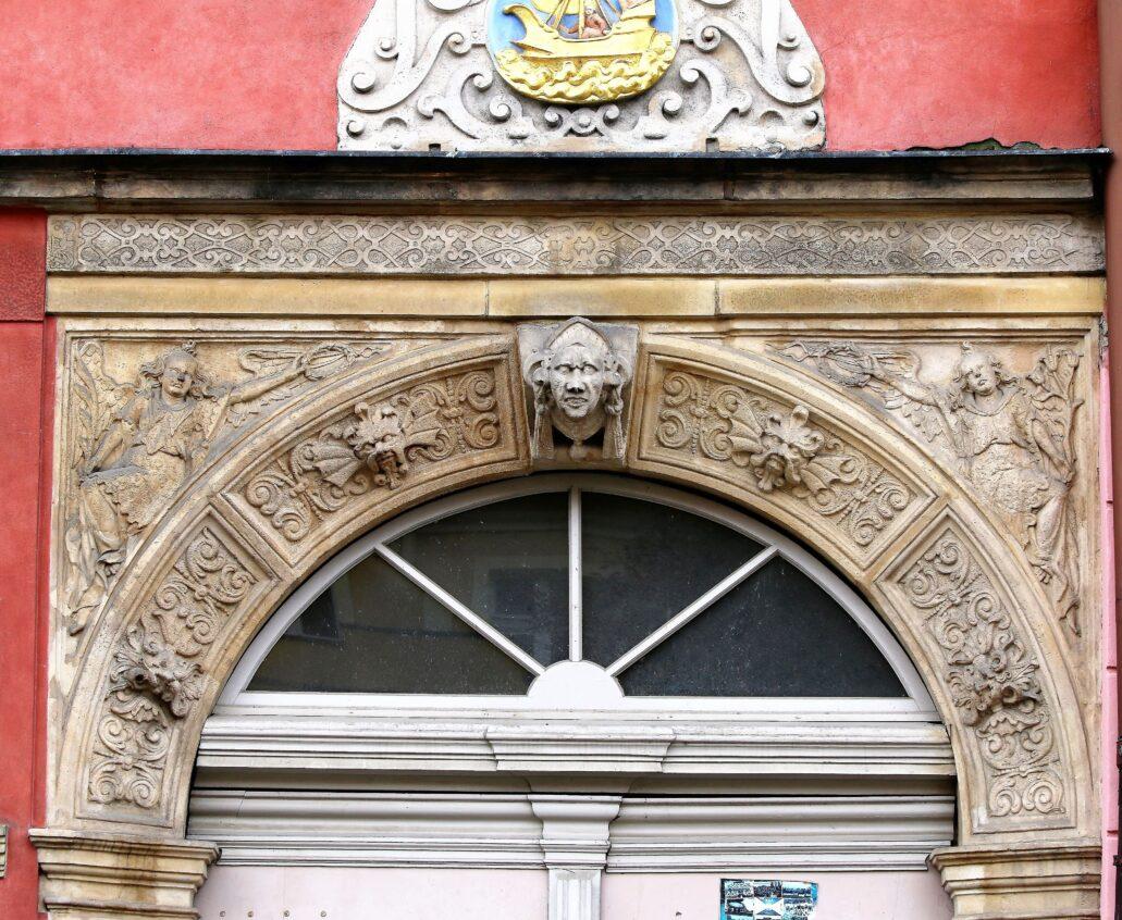 Świdnica. Rynek 26. Zwieńczenie portalu kamienicy z nieco kaprawymi aniołami, trzymającymi wieńce sławy oraz przetworzonym, barokowym ornamentem wstęgowo-cęgowym. Fot. Jerzy S. Majewski