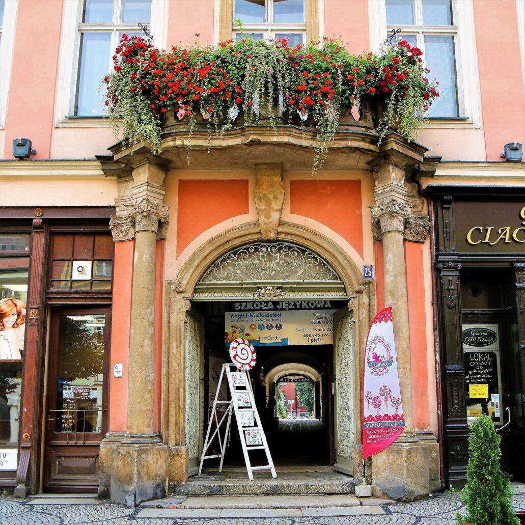 Świdnica. Rynek 25. Barokowy portal najwspanialszej spośród wszystkich kamienic wokół rynku zwanej pałacem Hochbergów. Do tego arystokratyczne rodu, jednego z najbogatszych na Śląsku, właścicieli zamku w Książu, kamienica należała przez niemal sto lat od 1694 r. Zakupił ją hrabia Hans Heinrich Hochberg. Przebudowy dokonał już kolejnym stuleciu, około 1730 r. jego następca, hr. Konrad Ernst Maksymilian, zaś prace budowalne powierzono wg Sobiesława Nowotnego – mistrzowi budowlanego z Sobótki – Wenzelowi Mattauschowi. Fot. Jerzy S. Majewski