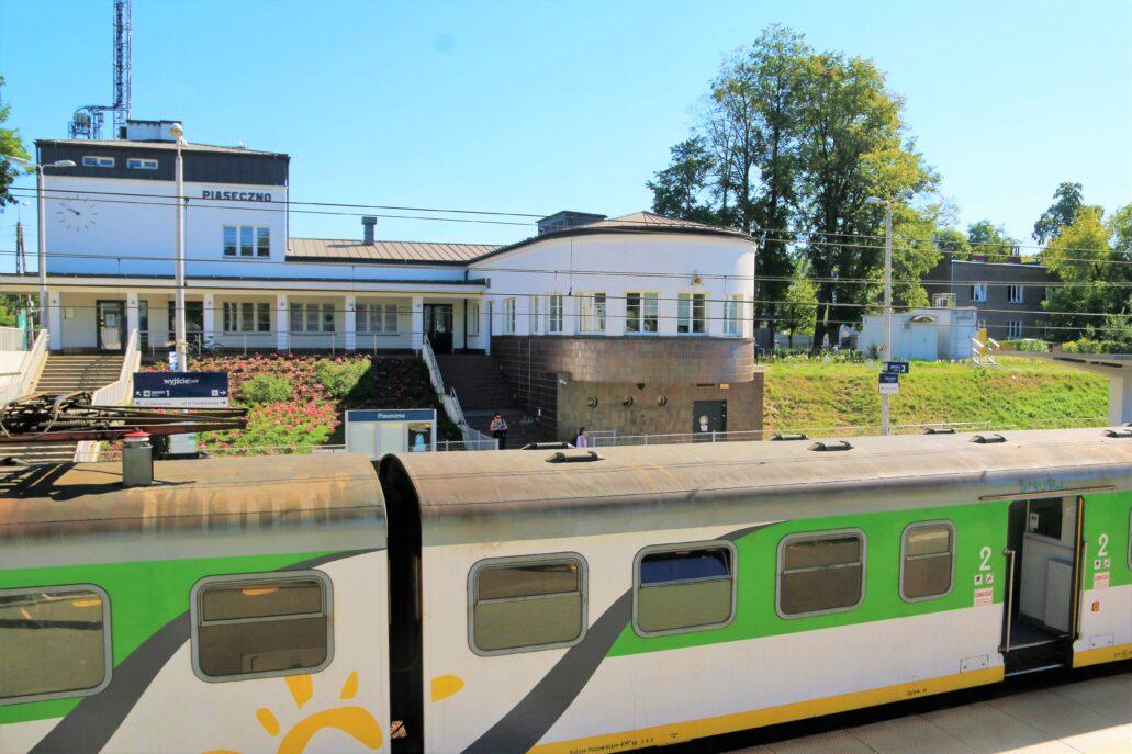 Piaseczno. Dworzec kolejowy widoczny od strony peronu. Budynek usytuowany jest ponad głębokim wykopem mieszczącym perony. Zaprojektowany został na rzucie litery L. W skrzydle widocznym z prawej strony, częściowo nadwieszonym i zamkniętym półkoliście, mieściła się pierwotnie nastawnia semaforów. W trakcie remontu przeprowadzonego kilka lat temu skrzydło to przeznaczono na umieszczenie restauracji z zapleczem. W głębi po lewej widoczny podcień stanowiący niejako przedłużenie sali z kasami i poczekalnią. Fot. Jerzy S. Majewski
