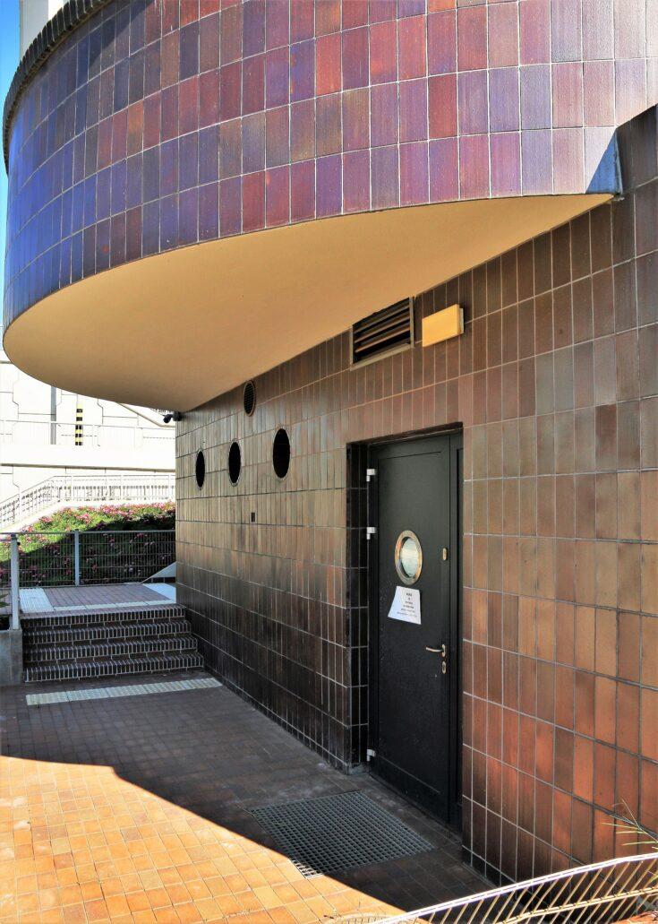 Piaseczno. Dworzec kolejowy. Nadwieszone zaokrąglenie skrzydła mieszczącego pierwotnie nastawnię semaforów. Uwagą zwracają okrągłe, okrętowe okienka w ścianie obłożonej klinkierem. W trakcie remontu projektanci bardzo dobrze zaprojektowali do tego miejsca nowe drzwi. Fot. Jerzy S. Majewski