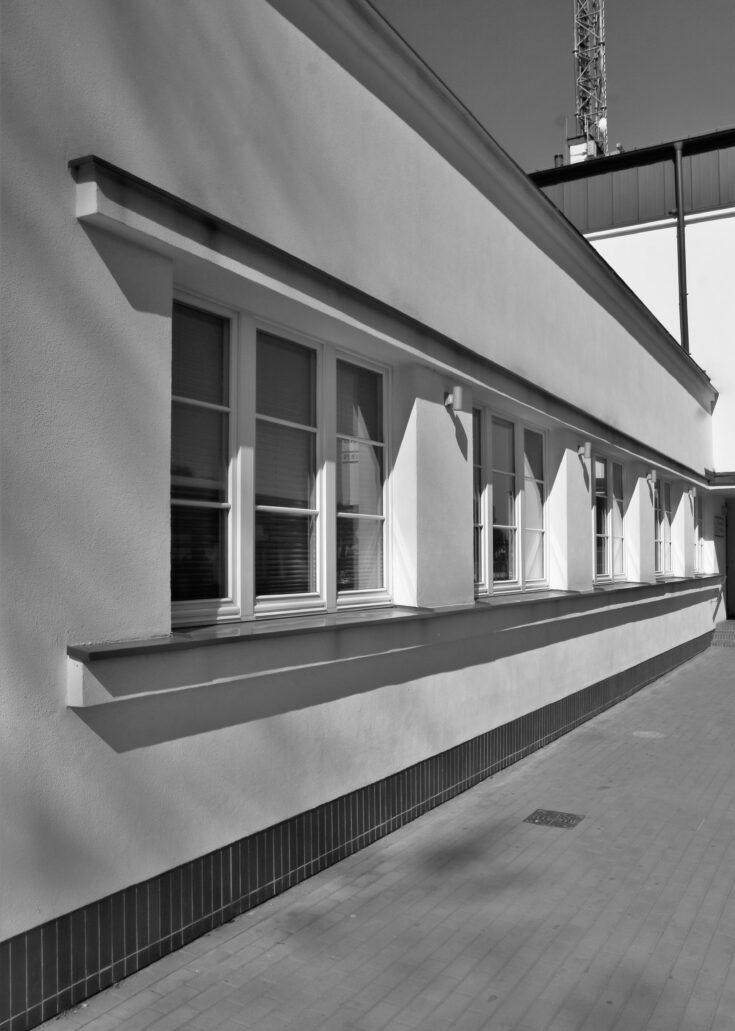Piaseczno. Dworzec kolejowy. Leżące okna, oświetlające wnętrze sali kasowej i poczekalni od zewnątrz, ujęte zostały we wspólne obramowanie, tworzące wrażenie długiego, le corbusierowskiego okna wstęgowego. Od góry obramienie to harmonijnie zbiega się z daszkiem ujmującym podcień z wejściem do budynku. Fot. Jerzy S. Majewski