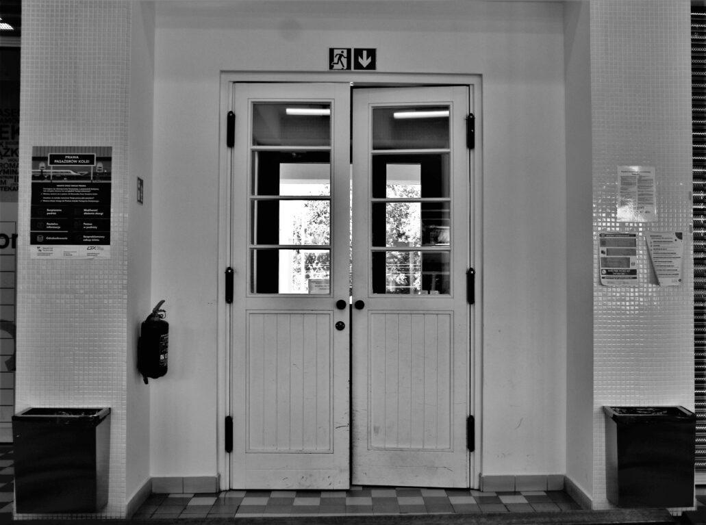 Piaseczno. Dworzec kolejowy. Podwójne, wahadłowe drzwi wejścia wiodącego z poczekalni do podcieni i wprost na schody prowadzące na peron. Fot. Jerzy S. Majewski