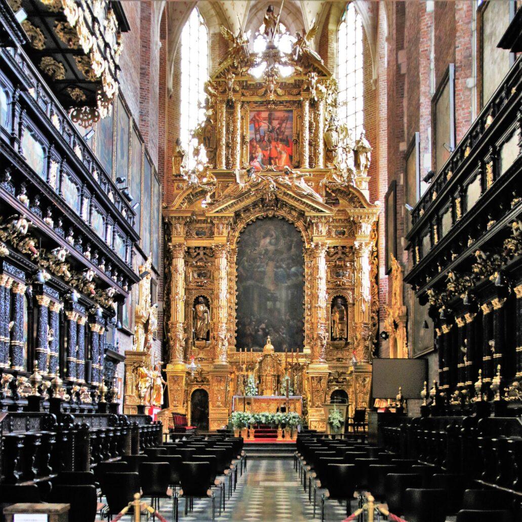 Kraków. Kościół Bożego Ciała. Ogromny, barokowy ołtarz świątyni. W zwieńczeniu widać obraz Tomasza Dolabelli ze sceną Zdjęcia z Krzyża. Poniżej znacznie większy obraz Dolabelli ze sceną Narodzenia Chrystusa. Ołtarz zrealizowany w 1634 r. przez warsztat Baltazara Kuncza jest jednym z najbardziej jaskrawych przykładów horror vacui (lęku przed pustą przestrzenią) w sztuce Rzeczpospolitej XVII wieku. Zwykły obiektyw aparatu fotograficznego zdaje się szaleć, nie mogąc ustawić ostrości na odbijającym światło pozłacanym ornamencie (także w nastawach ręcznych). Ornament ten zapełnia dosłownie każdy centymetr kwadratowy drewnianej powierzchni ołtarza. W takiej oprawie stłoczone postaci na obrazie Zdjęcia z Krzyża zdają się tchnąć umiarem. Fot. Jerzy S. Majewski