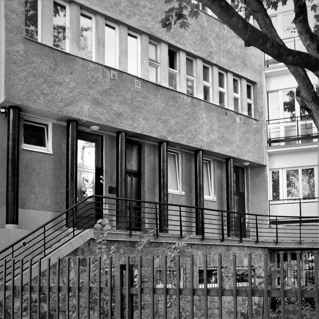 Warszawa. Sewerynów 4. Tylna elewacja wieży od dziedzińca opracowana została w estetyce le corbusierowskiego funkcjonalizmu. Partia przyziemia jest lekko podcięta i wsparta na rzędzie czarnych słupów. Okna pięter zgrupowane zostały w długie wstęgi. Budynek od strony Skarpy wsparty jest na podstawie licowanej polnym kamieniem. Widoczny powyżej ganek łączy wszystkie trzy klatki schodowe kamienicy. Fot. Jerzy S. Majewski