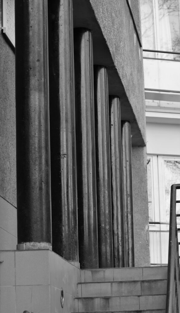 Warszawa. Sewerynów 4. Rząd czarnych słupów u podstawy tylnej elewacji wieżowej części budynku. Fot. Jerzy S. Majewski