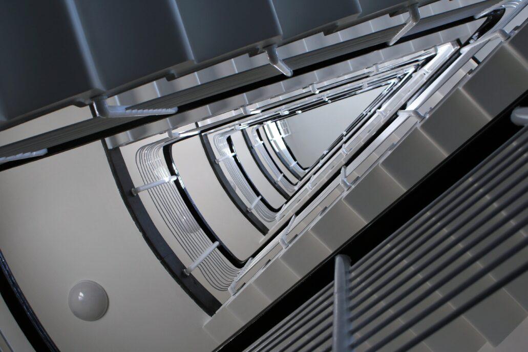 Warszawa. Sewerynów 4. Trójkątna dusza głównej klatki schodowej. Jest to jedno z najbardziej efektownych wnętrz warszawskich klatek schodowych z lat 30. XX w. Sposób jej opracowania z ażurowymi schodami okładanymi lastrykiem jest unikatowy. Sam trójkątny kształt klatki był wypadkową rzutu budynku o dwóch skrzydłach ustawionych do siebie pod kątem rozwartym. Klatka znalazła się w narożniku i jej boczne ściany są równoległe do ścian zewnętrznych obu skrzydeł kamienicy. Fot. Jerzy S. Majewski