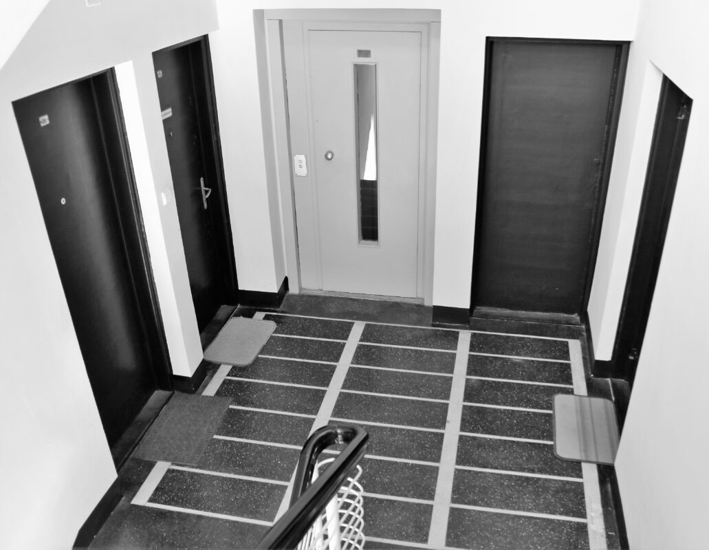 """Warszawa. Sewerynów 4. Klatka schodowa w wieżowej części budynku. Wszystkie drzwi do mieszkań były politurowane na czarno (dąb) z wcieranymi w słoje brązem aluminiowym. Wydaje się, że podobnie wyglądały drzwi do wind. Niestety dziś to sztampowe drzwi do półautomatycznych wind z czasów późnego PRL-u. Pierwotnie w budynku działały windy warszawskiej firmy """"Gronowski S.A."""" Fot. Jerzy S. Majewski"""
